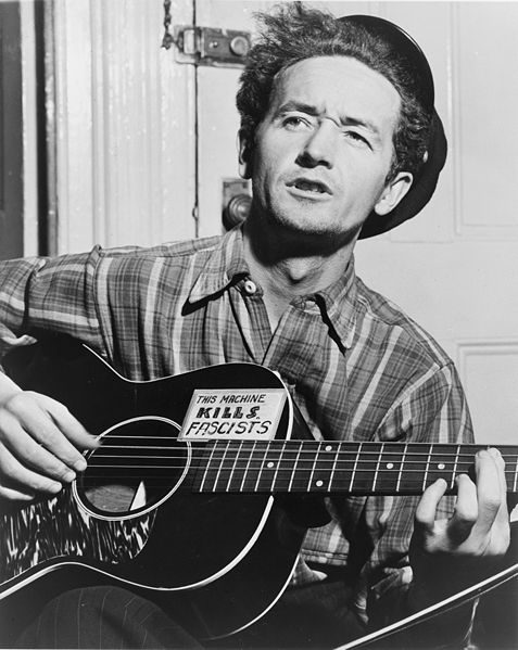 /uploads2/55165_2_27_2019_6_37_21_PM_-_57200_12_8_2008_8_53_49_AM_-_477px-Woody_Guthrie_NYWTS.jpg